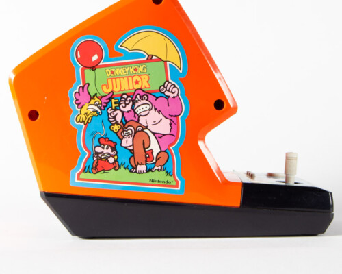 Side view of Donkey Kong Junior home console. Orange and black shell.