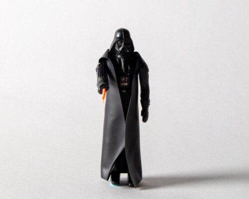 Front view of Darth Vader action figure pointing lightsaber forward.