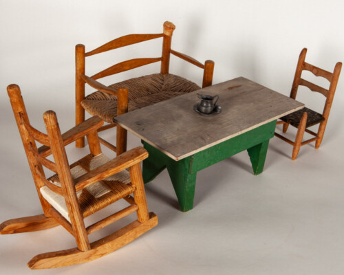 Dollhouse table and wooden chair. Metal jug and basin on tabletop.