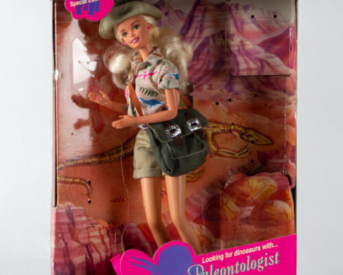 Paleontologist Barbie in original packaging. Doll is blonde and wearing khaki shorts and a dinosaur print work shirt with a canvas bag.