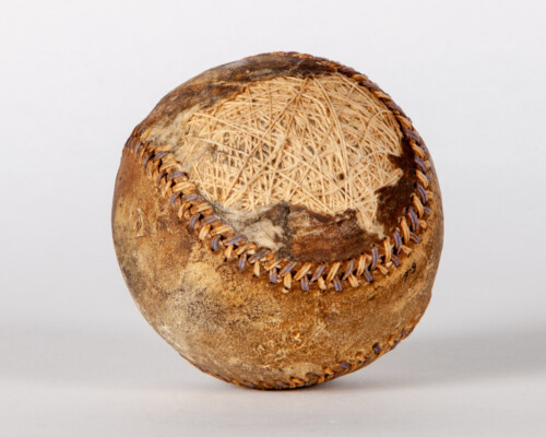 Aged baseball with multi-colored laces and a damaged surface.
