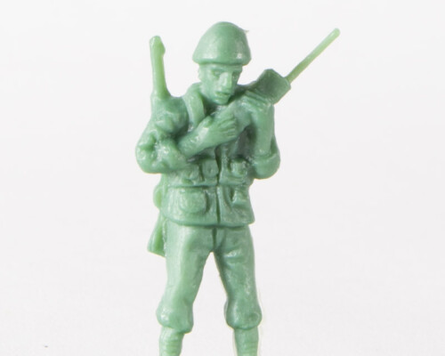 Tan plastic army man speaking on a radio with a rifle on his back.
