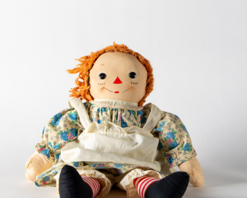 Side view of Raggedy Anne doll sitting with short hair and blue and tan floral dress.