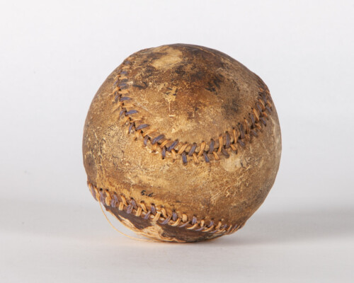 Close up of aged baseball. Surface is weathered and brown.