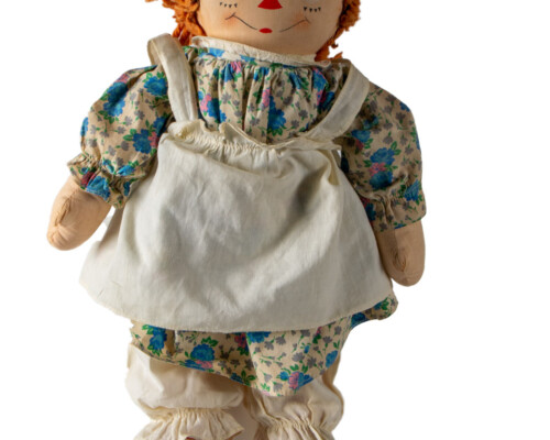 Front view of Raggedy Anne doll with short hair and blue and tan floral dress.