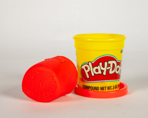 Red Play-Doh cylinder next to yellow and red cylindrical container.