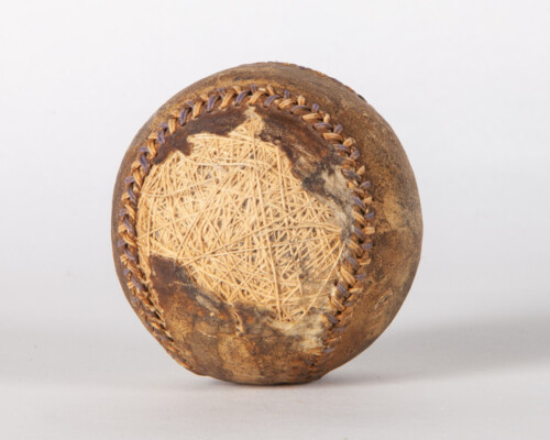 Close up of aged baseball. Surface is damaged and shows surface underneath.