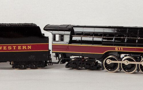 Side view of black and red train with gold and silver accents. with trailing coal car.